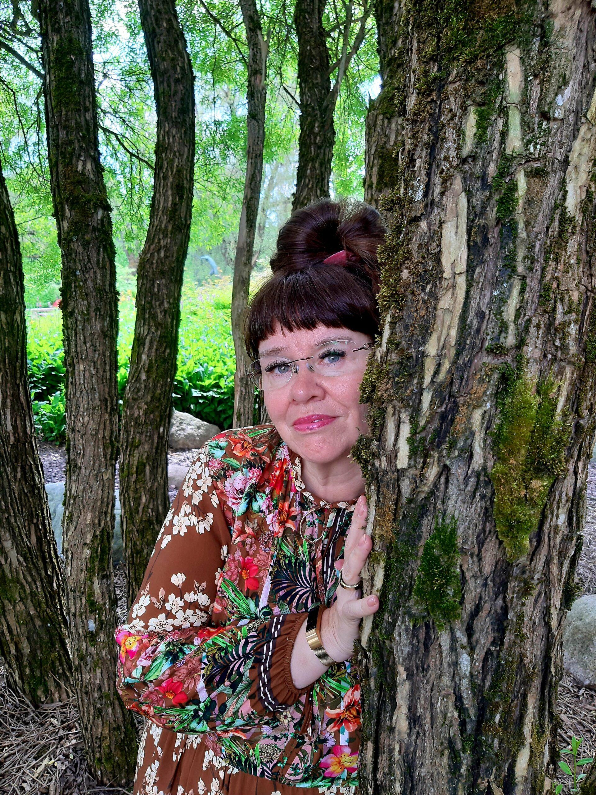 Nina kurkistaa puun takaa